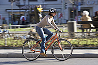 Germany, Bavaria, Munich, Mid adult woman riding bicycle - DSF000478