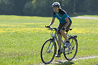 Germany, Bavaria, Mid adult woman riding bicycle - DSF000526