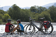 Germany, Bavaria, Man and woman sitting by bicycle - DSF000458