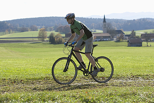 Germany, Bavaria, Mature man riding bicycle - DSF000453