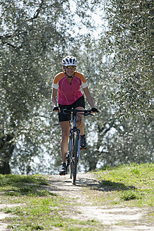 Italy, Mid adult woman riding bicycle - DSF000449