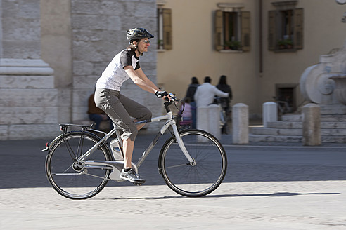 Italy, Arco, Mid adult woman riding electric bicycle - DSF000444