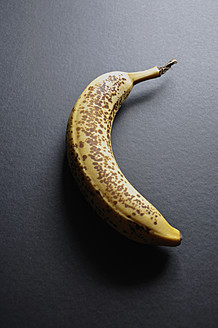Dark stained banana on black background, close up - AXF000001