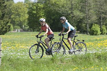 Germany, Bavaria, Women riding bicycle - DSF000537