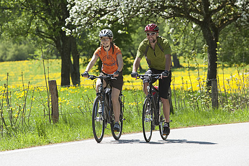 Germany, Bavaria, Man and woman riding bicycle - DSF000540