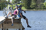 Germany, Bavaria, Man and woman sitting by bicycle - DSF000548