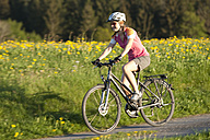 Germany, Bavaria, Young woman riding bicycle - DSF000556