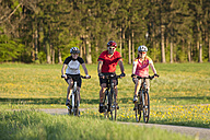 Germany, Bavaria, Man and women riding bicycle - DSF000554