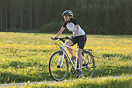 Germany, Bavaria, Mid adult woman riding bicycle - DSF000551