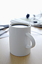 Cup of coffee, newspaper, mobile phone, pen and head set on office table, close up - TCF002314