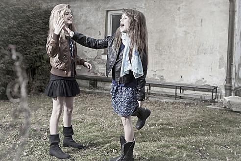 Germany, Bavaria, Two girls playing on backstreet - MAEF004525