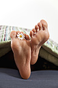 Germany, Bavaria, Human foot with flower on bed - MAEF004604