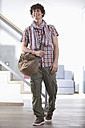 Germany, Bavaria, Young man standing with bag at home - MAEF004632