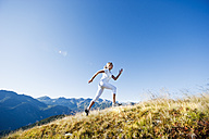 Austria, Salzburg County, Young woman running in alpine meadow - HHF004039