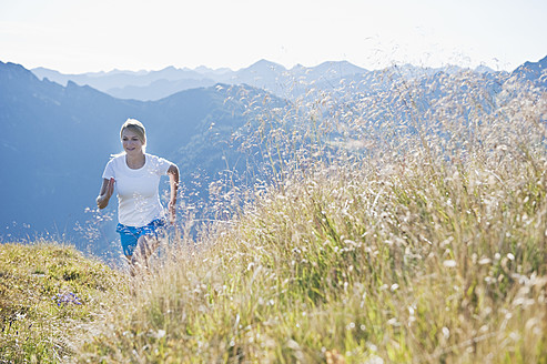 Austria, Salzburg County, Young woman running in alpine meadow - HHF004041