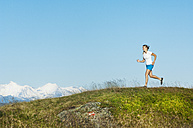 Austria, Salzburg County, Young woman running in alpine meadow - HHF004045