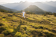 Austria, Salzburg County, Young woman running in alpine meadow - HHF004050