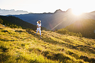 Austria, Salzburg County, Young woman running in alpine meadow - HHF004051