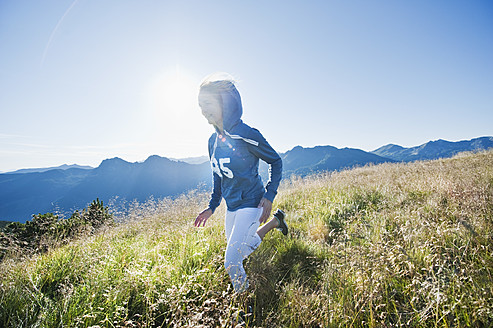 Austria, Salzburg County, Young woman running in alpine meadow - HHF004053