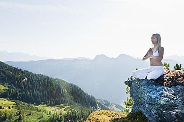 Austria, Salzburg County, Young woman sitting on rock and doing meditation - HHF004055
