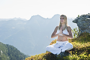 Austria, Salzburg County, Young woman sitting on rock and doing meditation - HHF004058