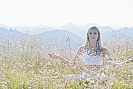 Austria, Salzburg County, Young woman sitting in alpine meadow and doing meditation - HHF004061