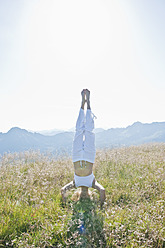 Austria, Salzburg County,, Young woman doing headstand in alpine meadow - HHF004064