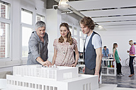 Germany, Bavaria, Munich, Man explaining architectural model to colleagues - RBYF000015