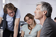 Germany, Bavaria, Munich, Mature man thinking while colleagues working in background - RBYF000076
