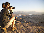 India, Karnataka, Young female tourist photographing on top of hill in Hampi - MBEF000323