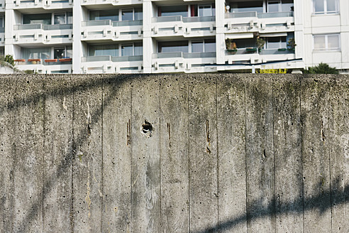 Germany, Bavaria, Munich Westend, Concrete wall in front of high rise - LFF000416