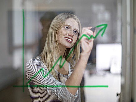 Germany, Cologne, Young woman drawing graph on glass - RHYF000089