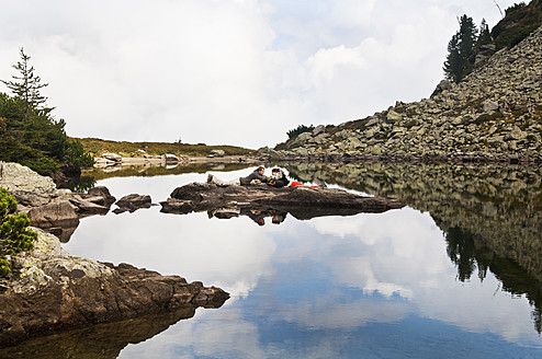 Austria, Styria, Man and woman lying on rock at Lake Spiegelsee - HHF004085