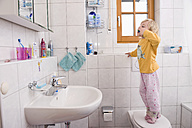 Girl standing on toilet, brushing teeth in bathroom - RNF000866