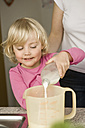 Mother and daughter pouring milk into measuring cup - RNF000914