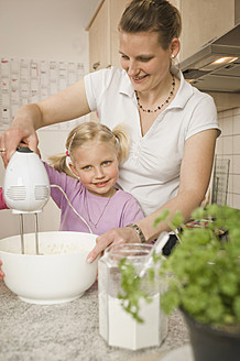 Mother and daughter mixing batter with electric whisk - RNF000920