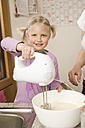 Mother and daughter mixing batter with electric whisk - RNF000921