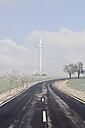 Germany, Saxony, View of empty road with wind turbine - MJF000010