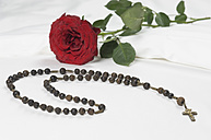 Rosary beads with red rose on bed, close up - CRF002193