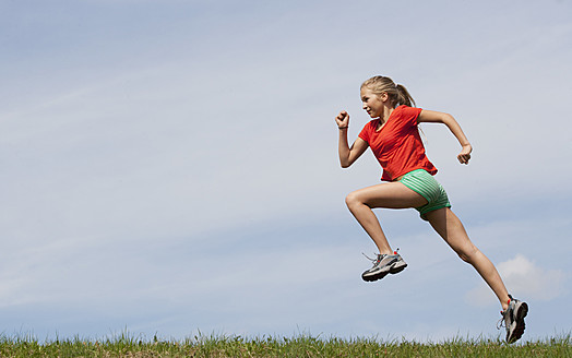Austria, Teenage girl running on grass - WWF002339