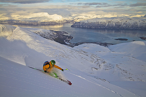 Norway, Lyngen, Skier skiing downhill at polar sea - FFF001299