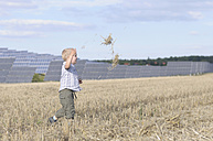 Germany, Saxony, Boy running in grass, solar panels in background - MJF000040