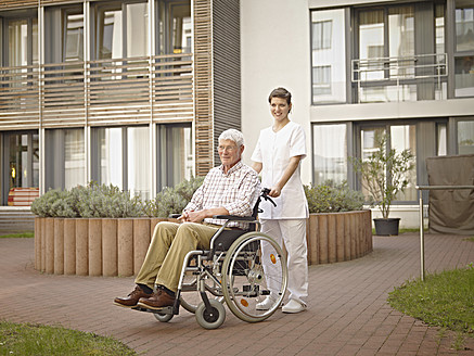 Germany, Cologne, Caretaker pushing senior man in wheelchair outside of nursing home - WESTF018664