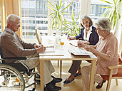 Germany, Cologne, Men on wheelchair with women sitting in nursing home - WESTF018682