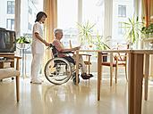Germany, Cologne, Senior women reading newspaper in wheelchair, Caretaker standing beside - WESTF018685