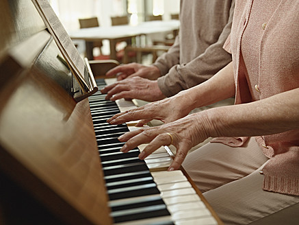 Germany, Cologne, Senior couple playing piano in nursing home - WESTF018703
