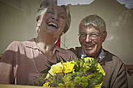 Germany, Cologne, Senior couple with flower bouquet, smiling - WESTF018721