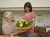 Germany, Cologne, Women holding bouquet in nursing home, smiling - WESTF018733