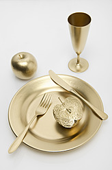 Golden cutlery with apple on white background - MUF001206