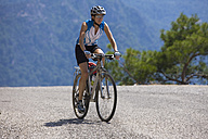 Turkey, Mid adult woman cycling through road - DSF000565